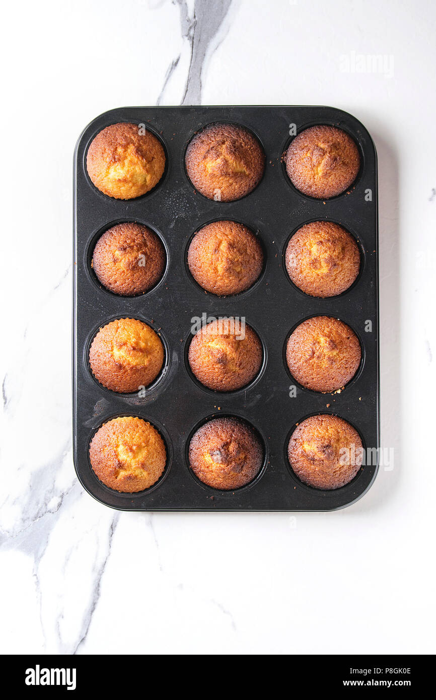 Fresh baked homemade lemon cakes muffins in black teflon baking dish over white marble background. Top view, space. - Stock Image