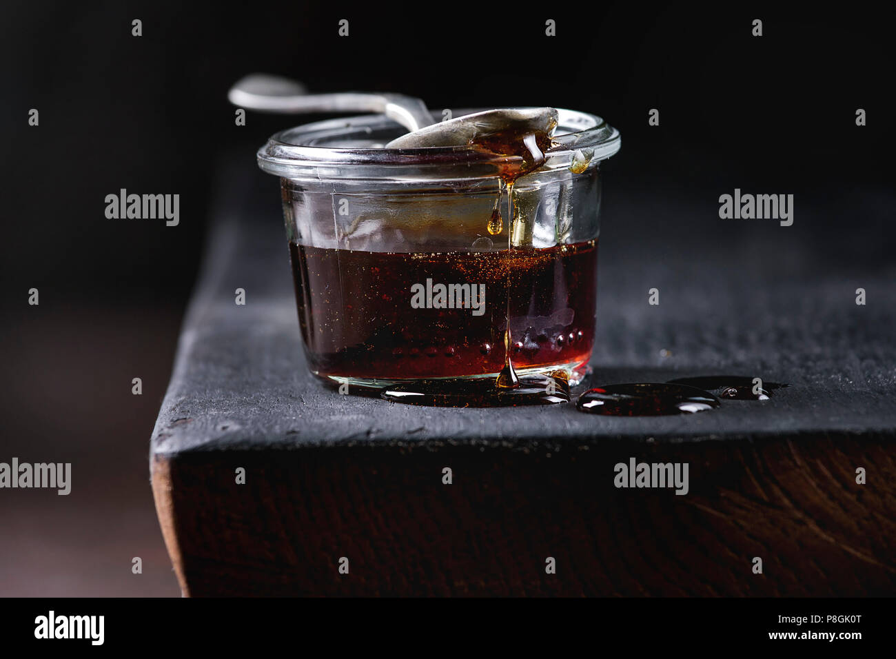 Homemade liquid transparent brown sugar caramel in glass jar standing on black wooden board with spoon. Close up - Stock Image
