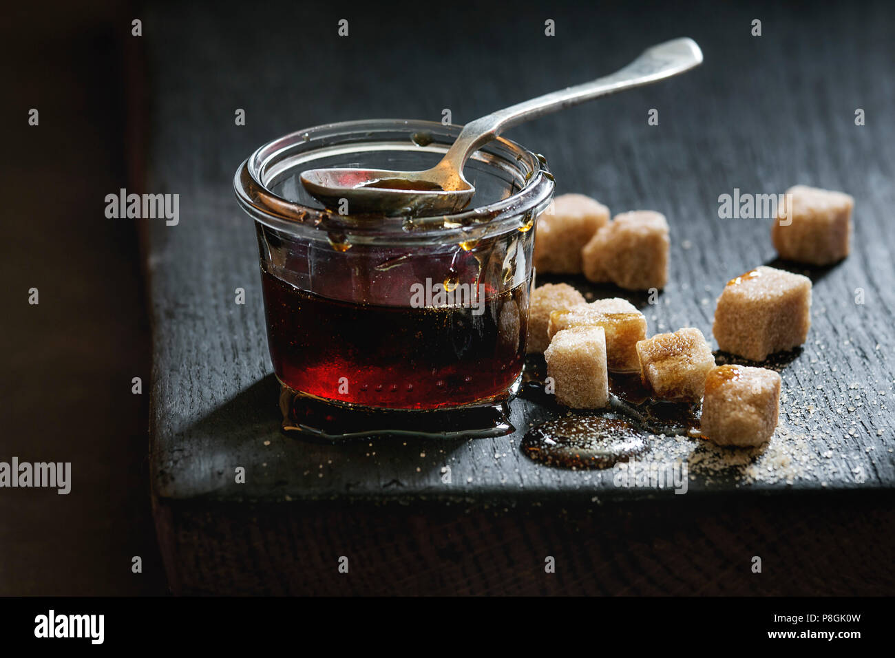 Homemade liquid transparent brown sugar caramel in glass jar standing on black wooden board with spoon and can sugar cubes. Close up. Day light - Stock Image