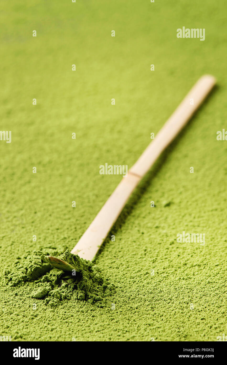 Green tea matcha powder in traditional bamboo spoon over powdering matcha as background. - Stock Image