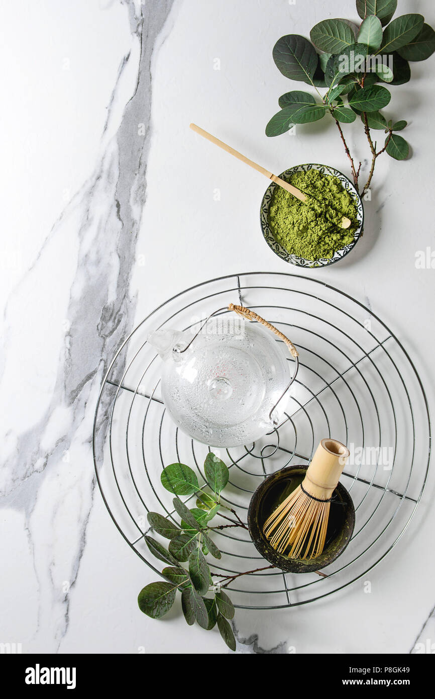 Ingredients for making matcha drink. Green tea matcha powder in ceramic bowl, traditional bamboo spoon, whisk on cooling rack, glass teapot, green bra - Stock Image
