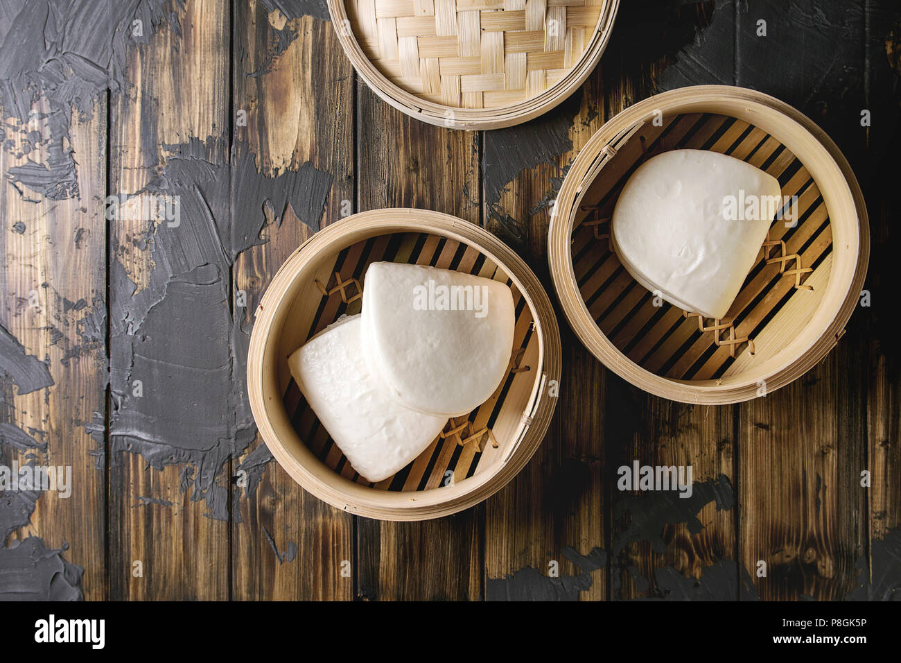 Empty gua bao steamed buns in opened bamboo steamer over dark wooden plank background. Flat lay, space. Asian fast food. - Stock Image
