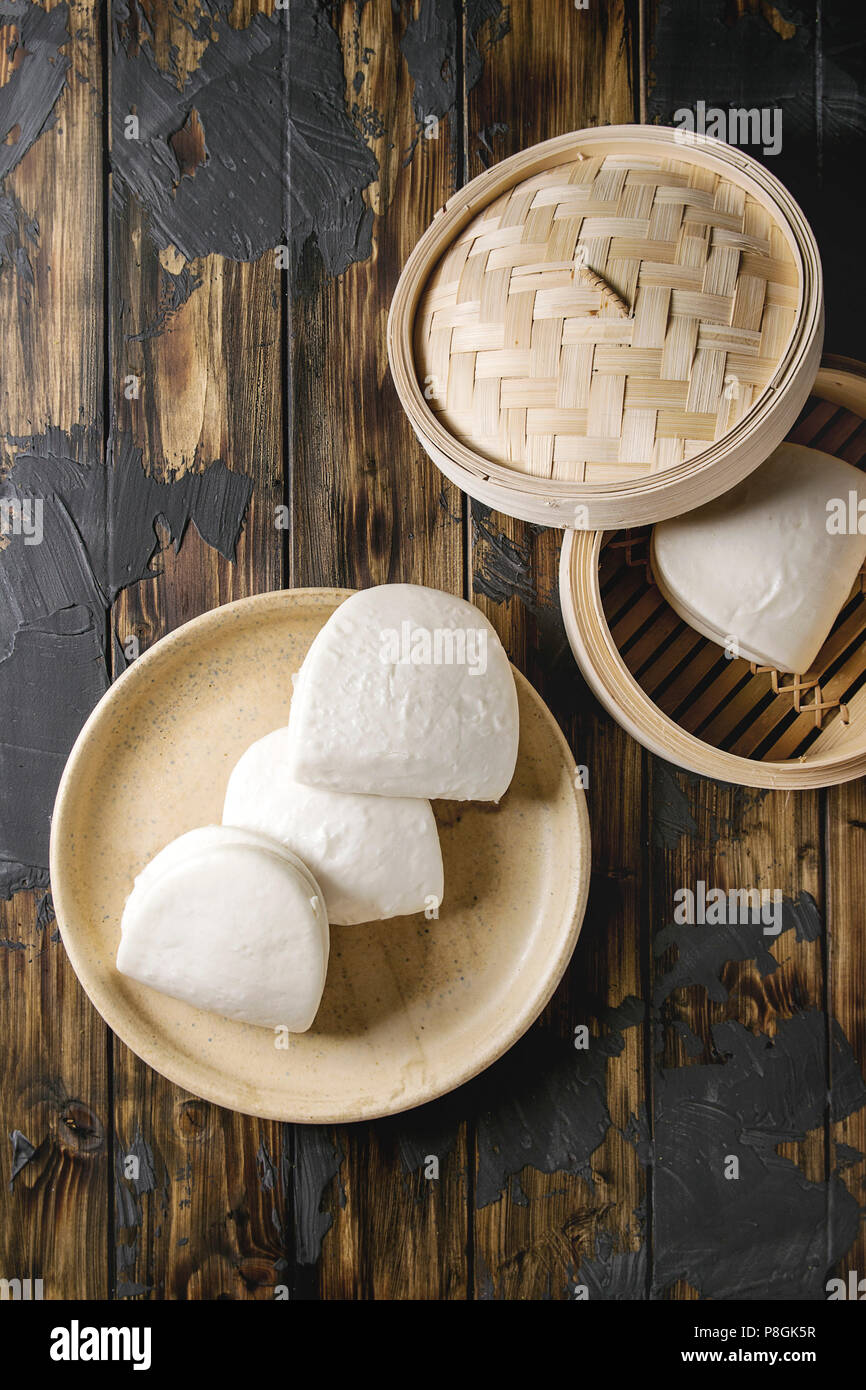 Empty gua bao steamed buns in ceramic plate and opened bamboo steamer over dark wooden plank background. Flat lay, space. Asian fast food. - Stock Image