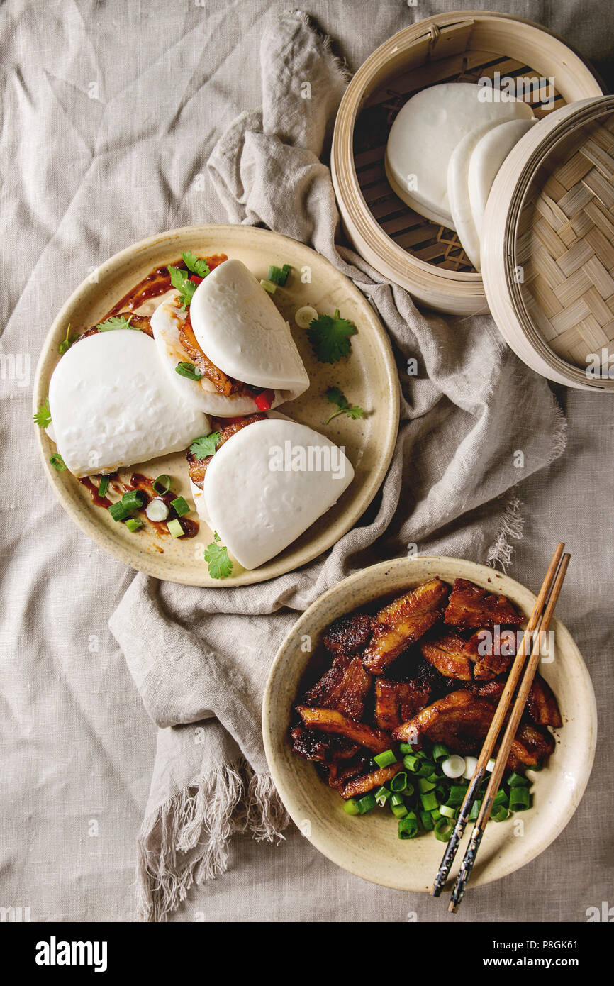 Asian sandwich steamed gua bao buns with pork belly, greens and vegetables served in ceramic plate over linen tablecloth. Asian style fast food dinner - Stock Image