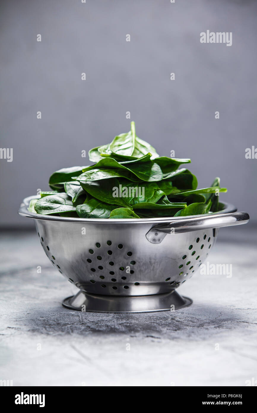 Spinach. Fresh organic spinach leaves in metal colander. Diet, dieting concept. Vegan food, healthy eating. Dark rustic style photo. Stock Photo