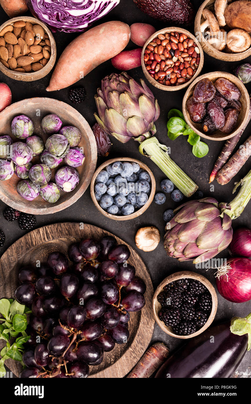 Assortment raw organic of purple ingredients: eggplants, artichokes, potatoes, onions, berries, nuts, carrots, brussel sprouts, grapes over dark backg - Stock Image