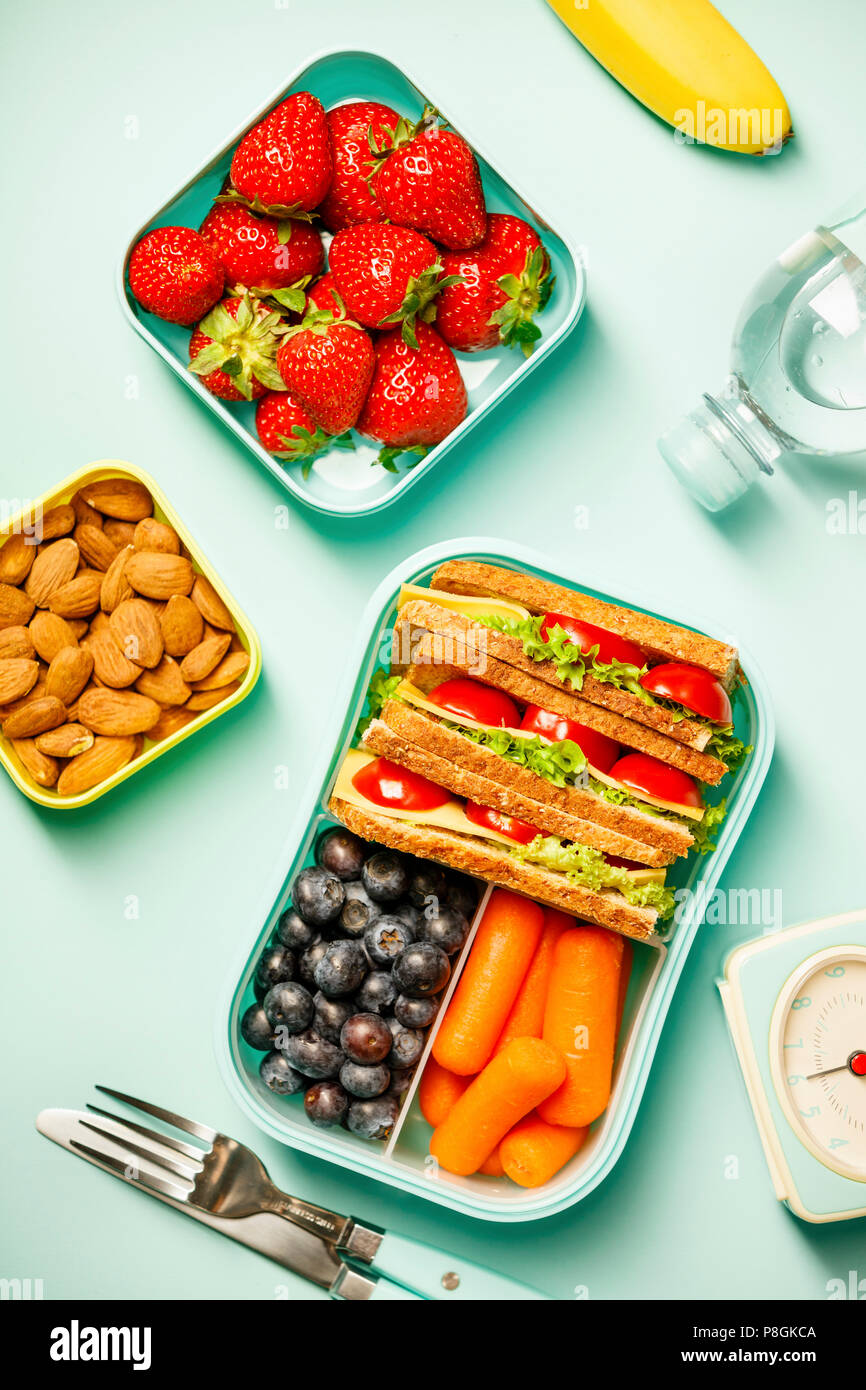 Creative flat lay with healthy lunch and office or school supplies on pastel colors background - Stock Image