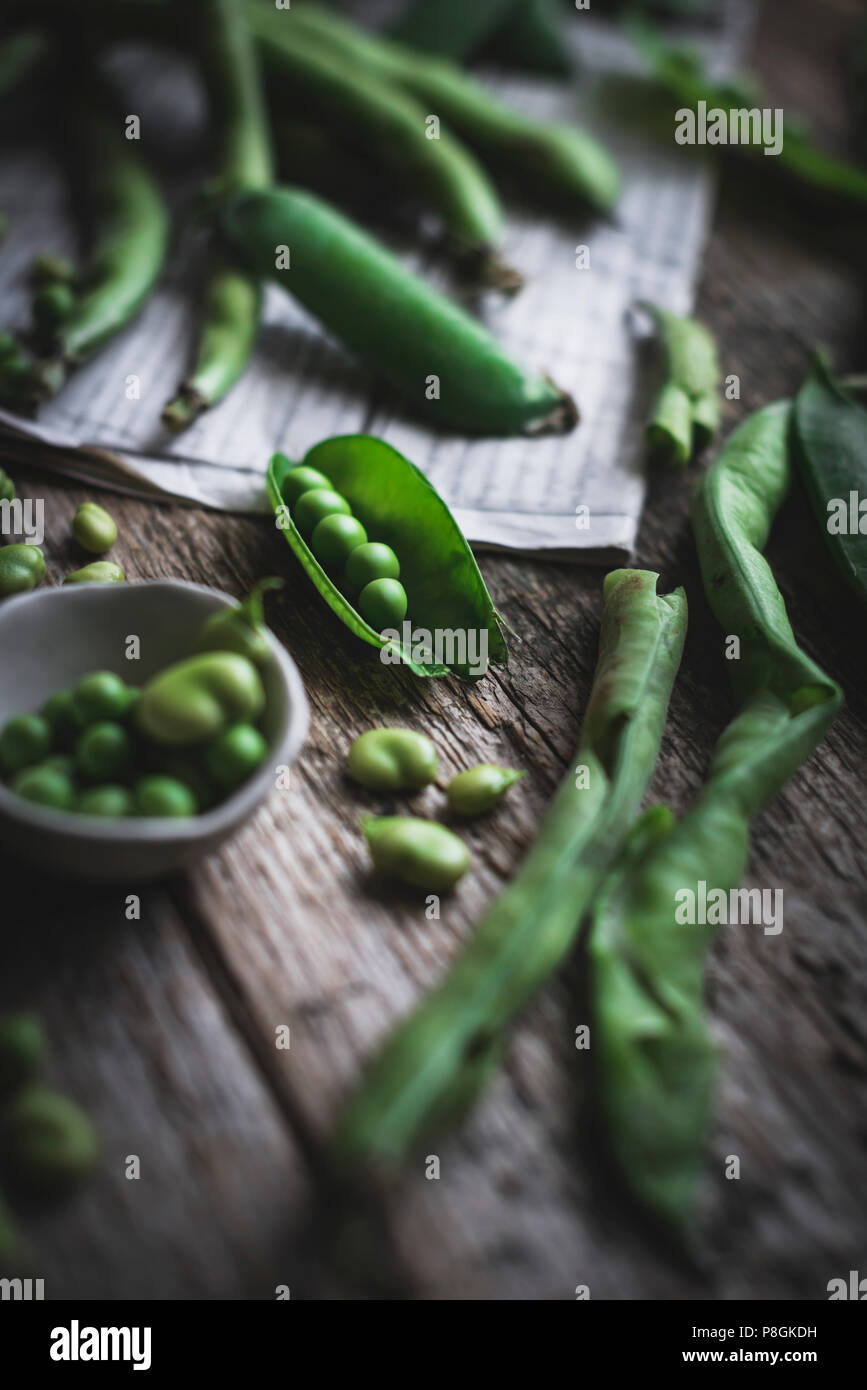 Peas in a pod and gren beans n a rustic kitchen table - Stock Image