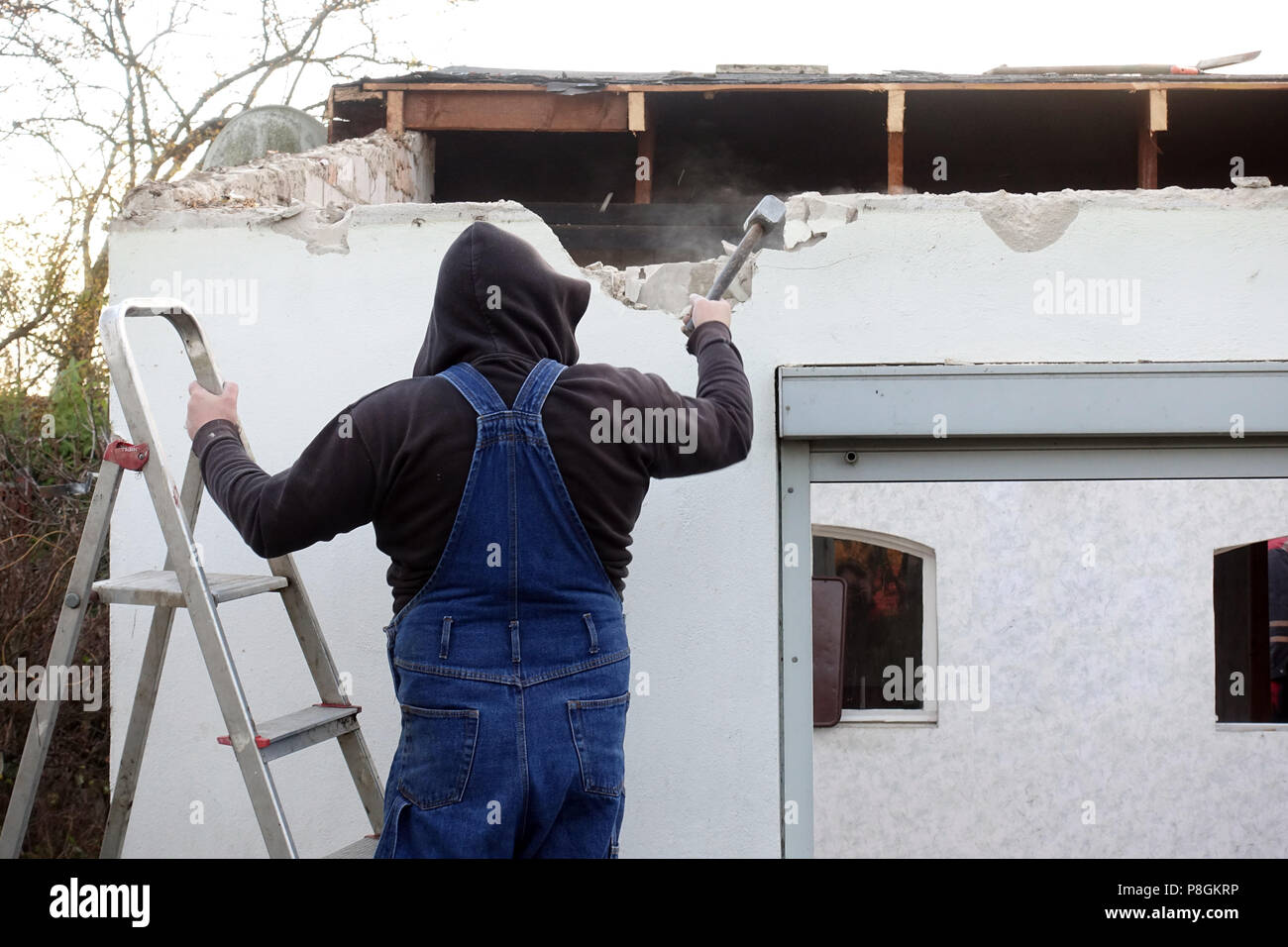 Berlin, Germany, artisan beating a wall in the rebuilding of a gazebo - Stock Image