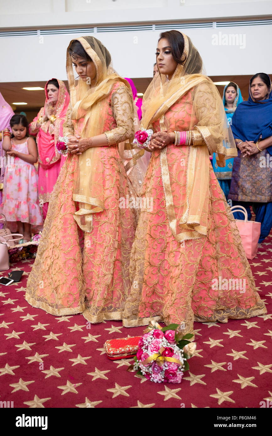 Two women in identical dresses at a wedding ceremony in the temple at the Sikh  Society in Richmond Hill, Queens, New York City. - Stock Image