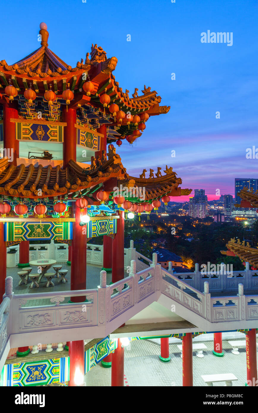 Thean Hou Buddhist Temple decorated with lanterns at dusk with the city skyline on the background, Kuala Lumpur, Malaysia - Stock Image