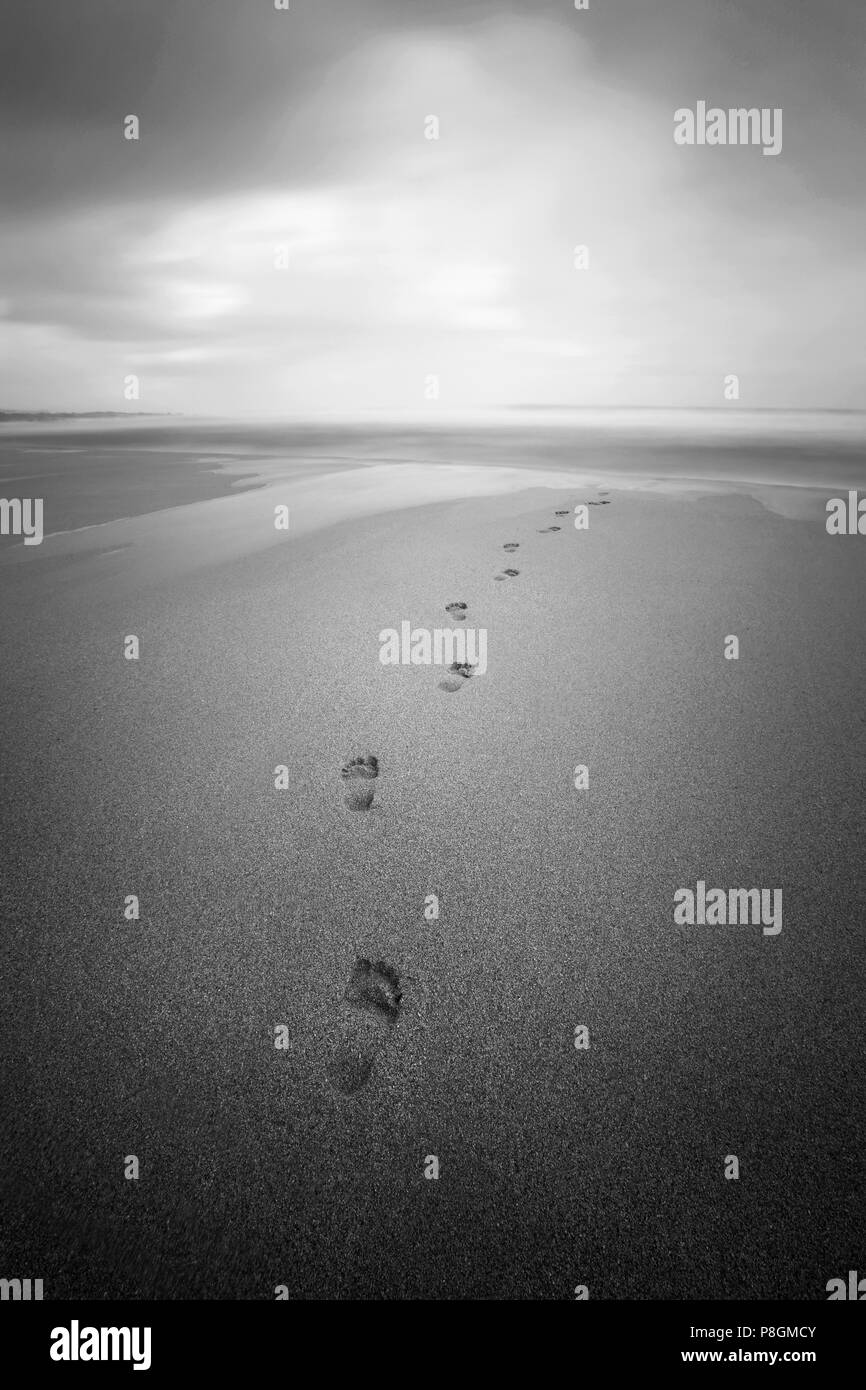 Footprints in the sand on a cloudy beach on a depressing day. - Stock Image