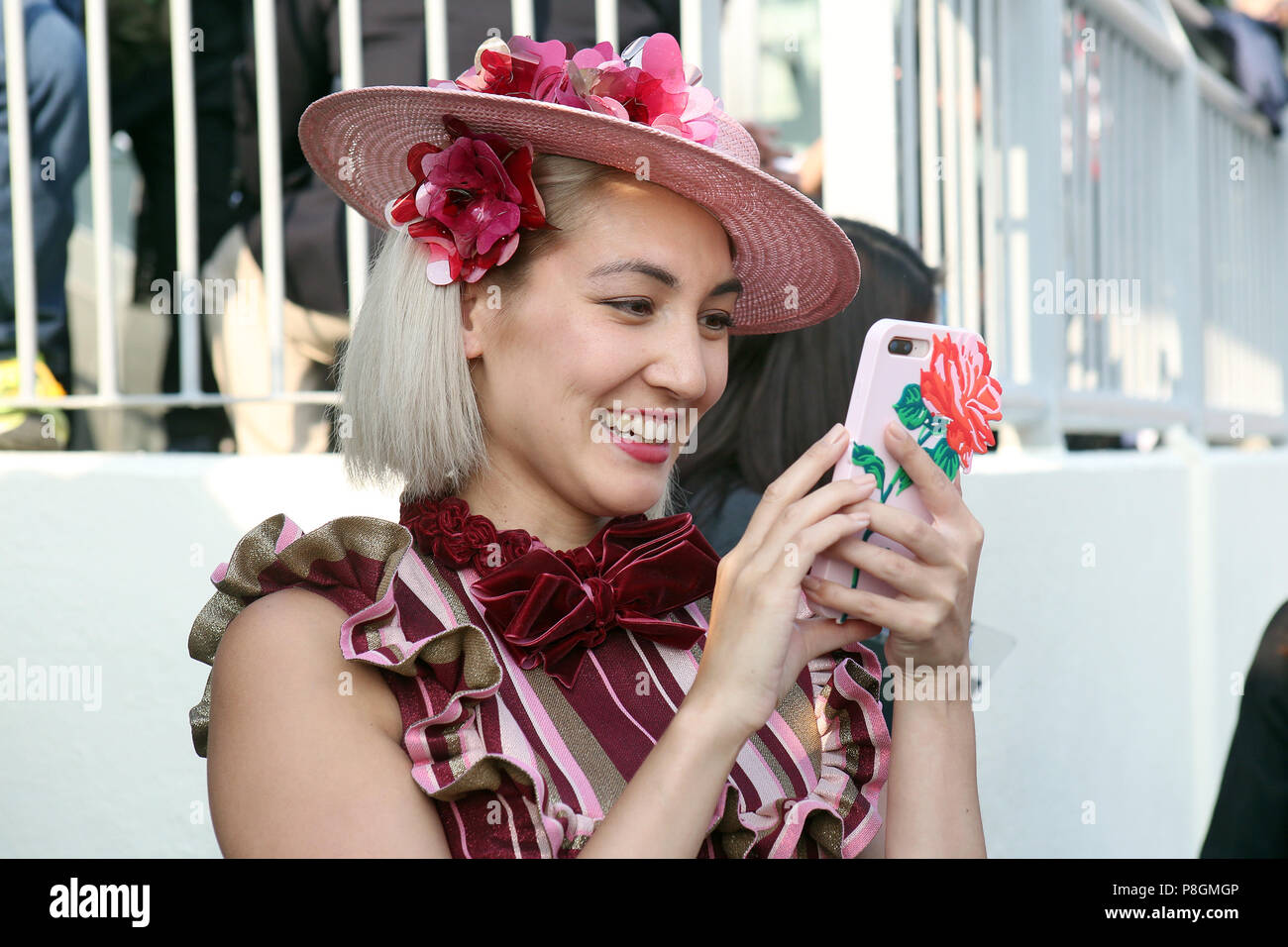Hong Kong, China, elegantly dressed Asian woman with hat photographed with her smartphone - Stock Image