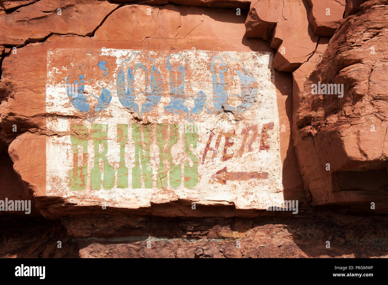 Fading 'Cold Drinks Here' ad painted on a red rock cliff near Mexican Hat, Utah, USA. - Stock Image