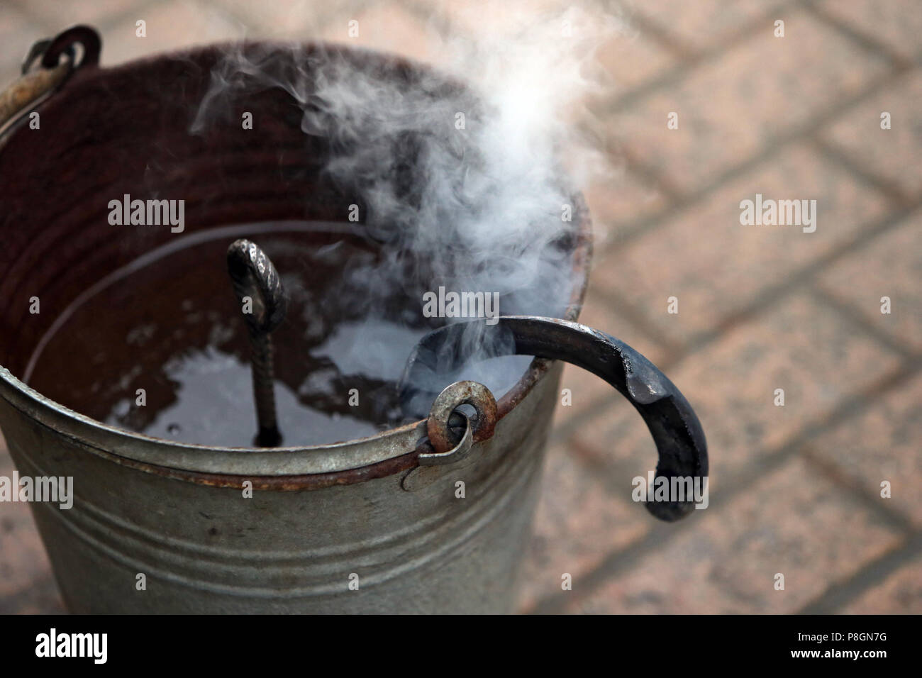 Neustadt (Dosse), heated horseshoe is cooled in a bucket of water - Stock Image