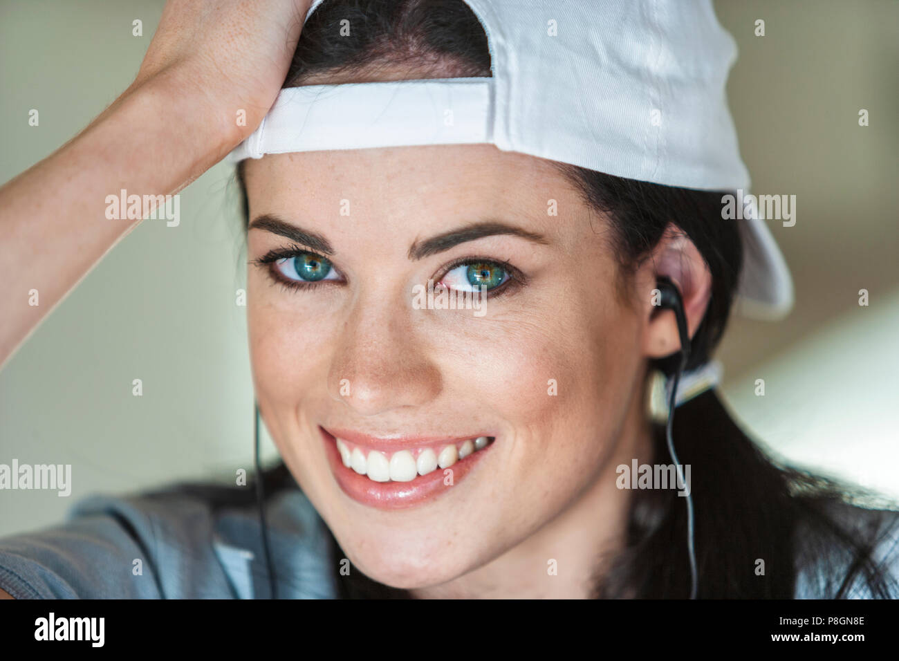 Portrait of young woman with earphones wearing a cap Stock Photo