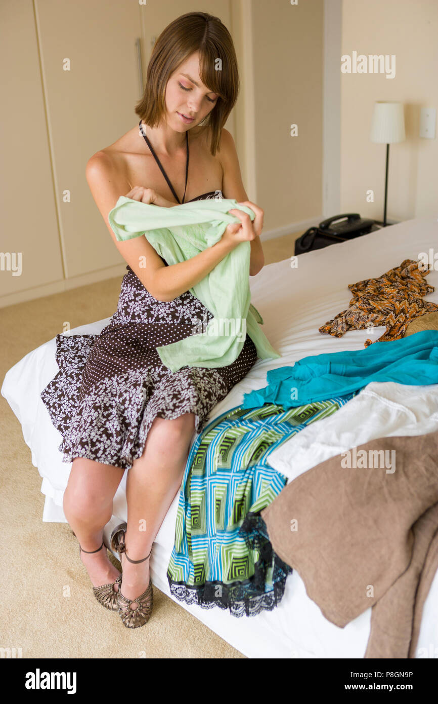 Young woman chooses clothing in bedroom Stock Photo