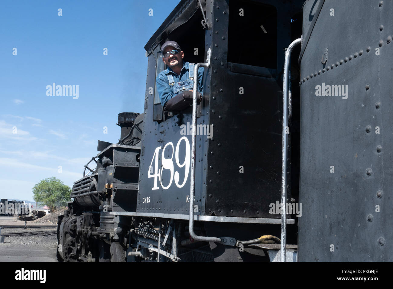 Portrait of a Train engineer on the Cumbres and Toltec scenic Railroad posing with the  restored steam engine 489, a K–39 mikado class locomotive - Stock Image