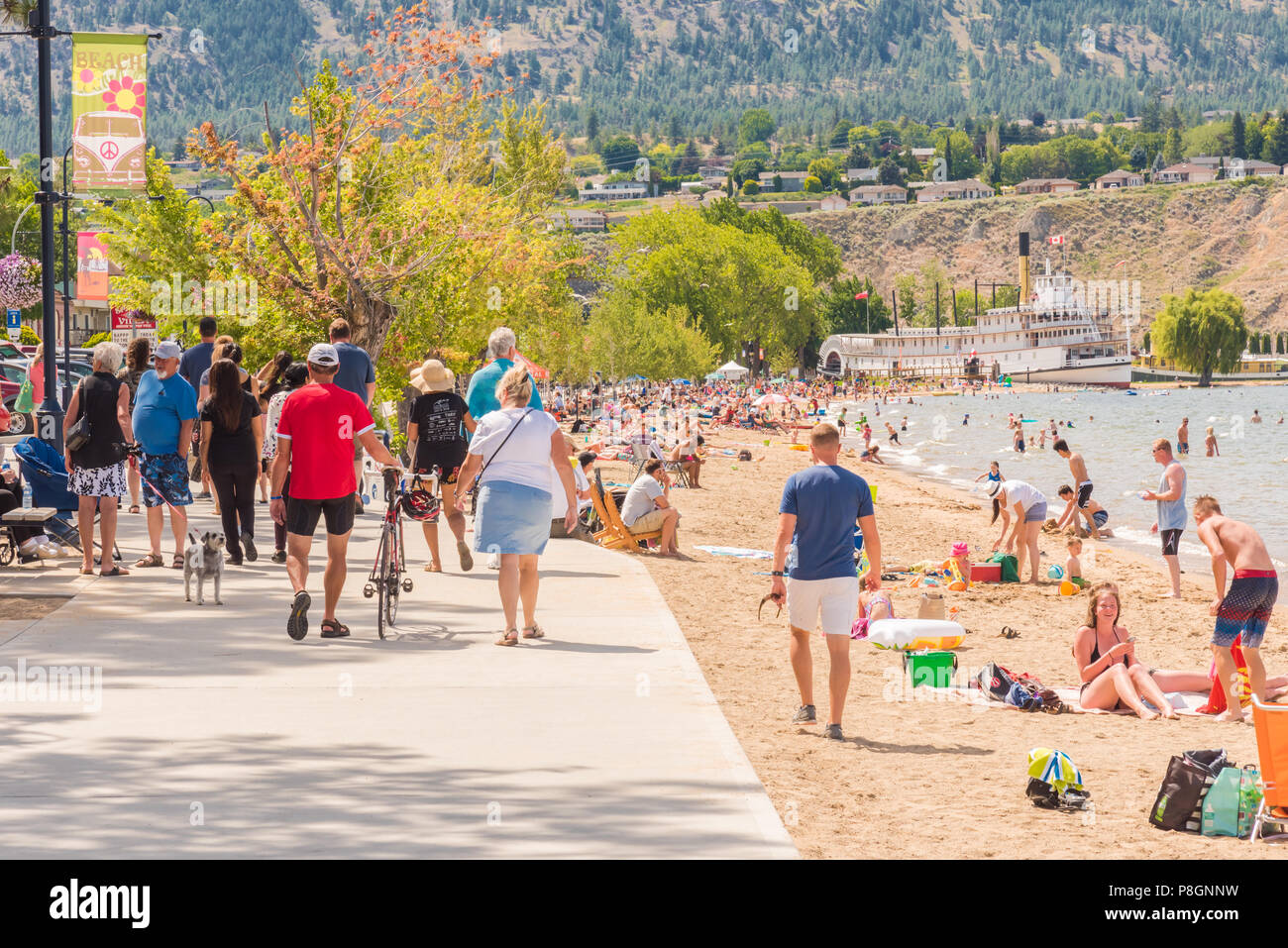 Penticton, British Columbia/Canada - July 7, 2018: tourists and locals walk along the lakeshore and enjoy the beach on Okanagan Lake on a hot summer d - Stock Photo