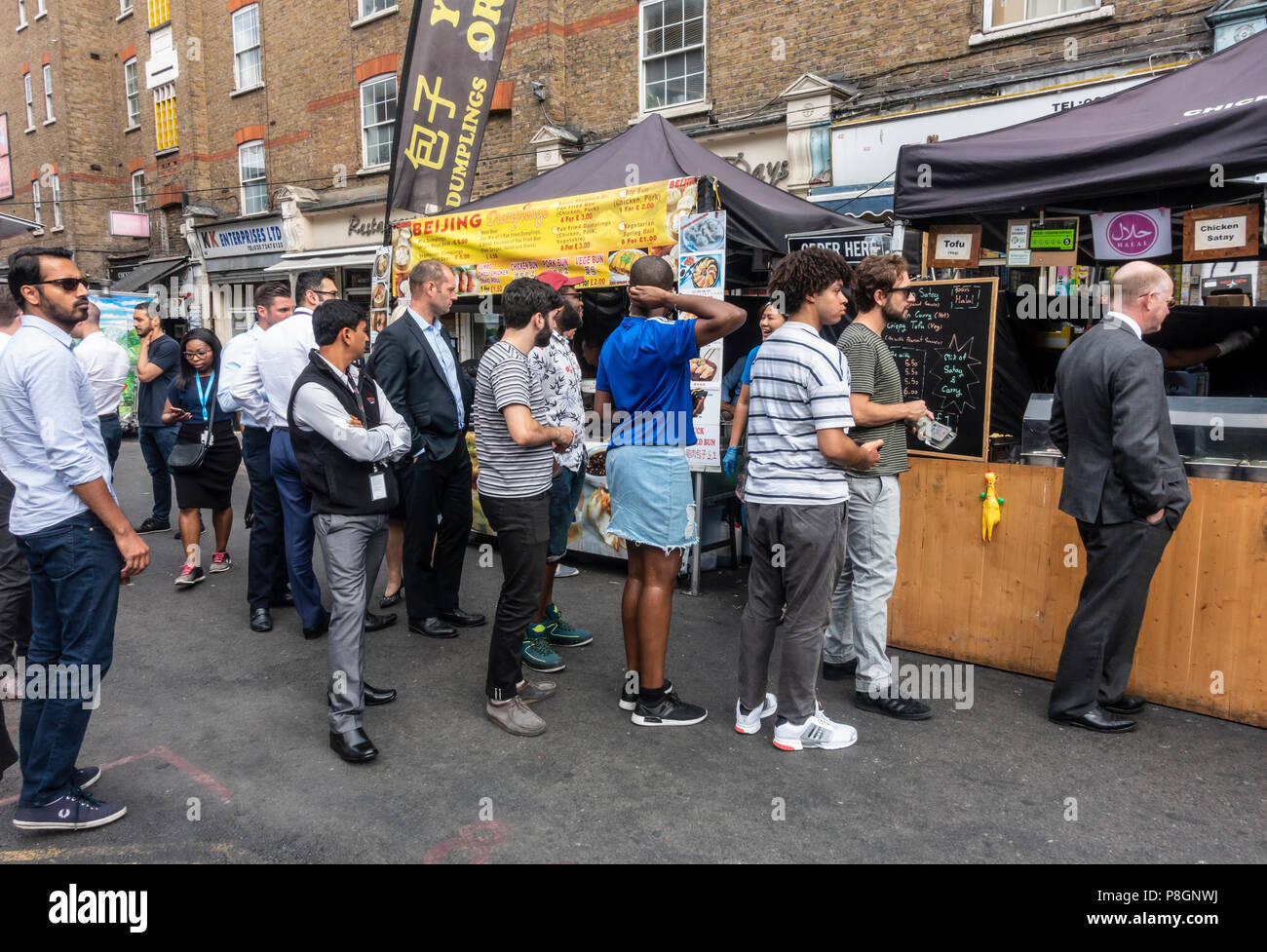 Local residents and workers queueing at two street food stalls in Petticoat Lane Market, Tower Hamlets, London, England, UK Stock Photo