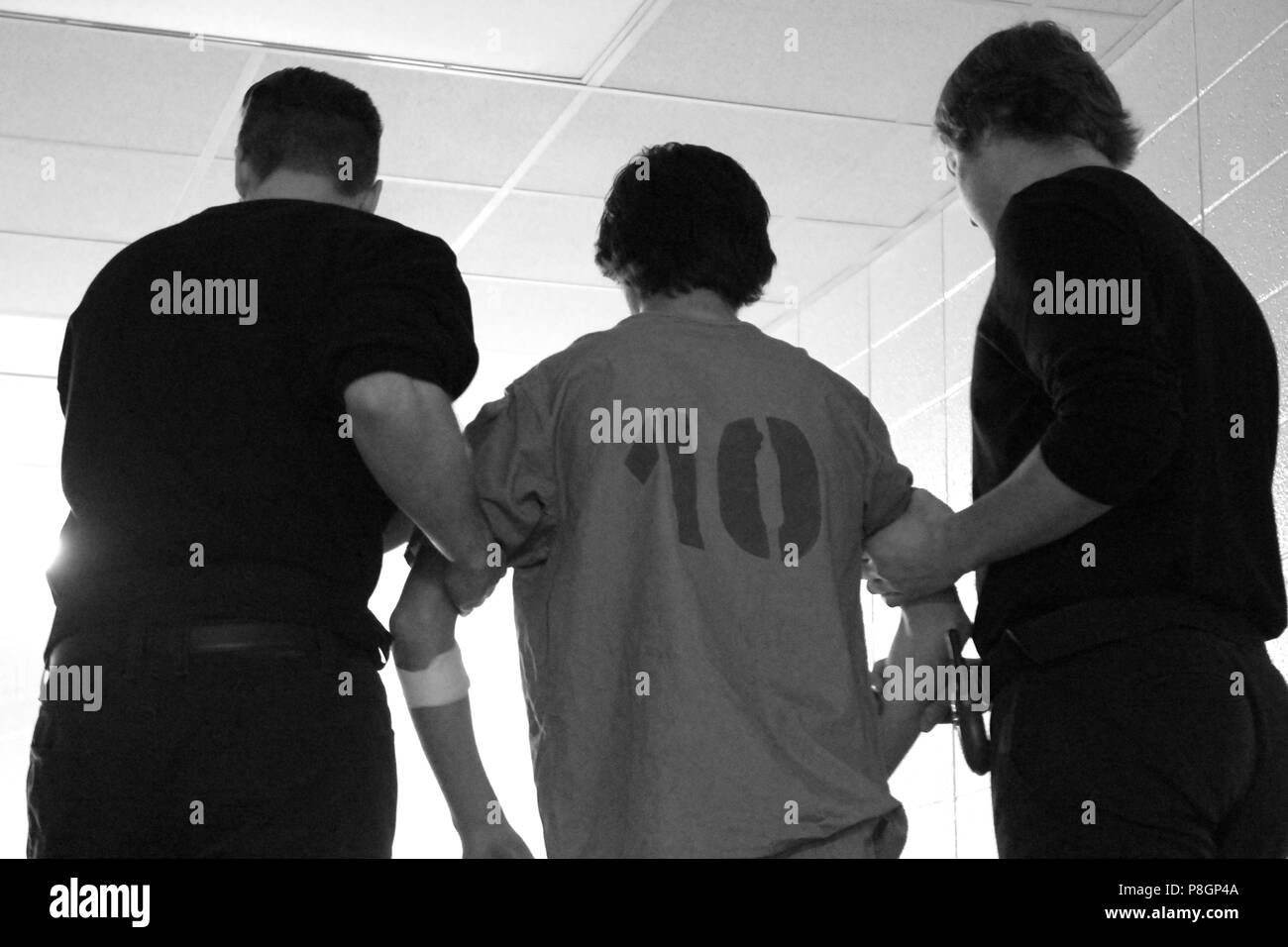 A prisoner in a jumpsuit with the number 10 is escorted by two guards. - Stock Image