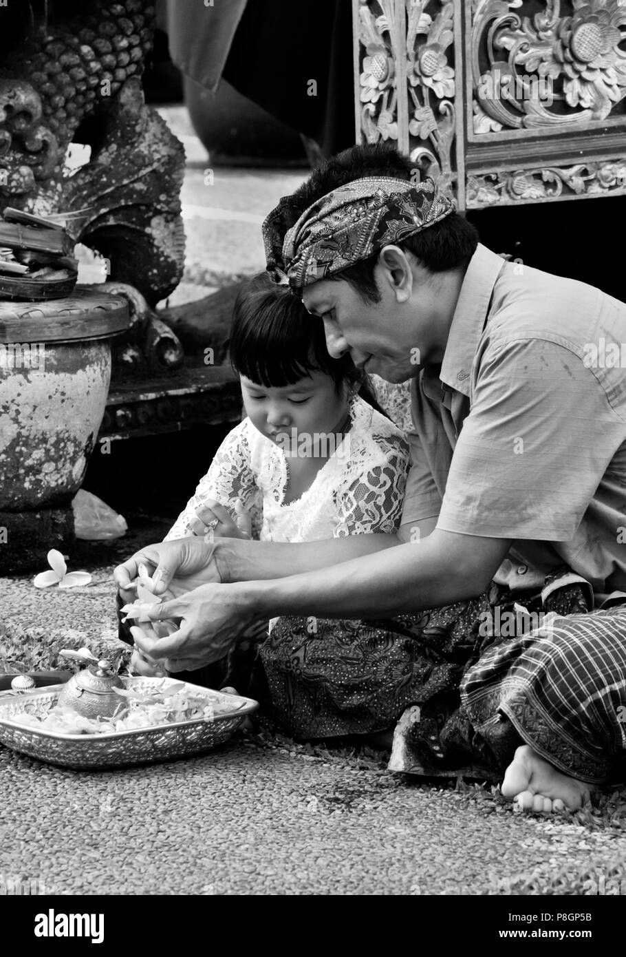 Father and daughter make puja at PURA TAMAN SARASWATI during the GALUNGAN FESTIVAL - UBUD, BALI, INDONESIA - Stock Image
