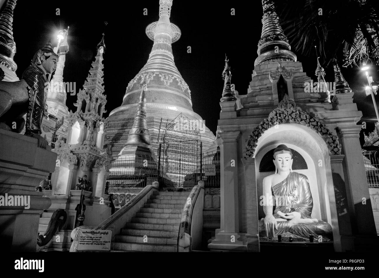 A BUDDHA STATUE and the main ZEDI of the SHWEDAGON PAGODA which dates from 1485 is gilded every year - YANGON, MYANAMAR Stock Photo