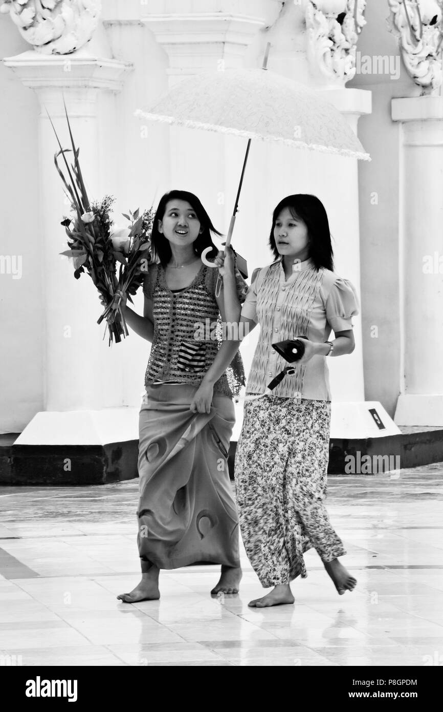 BURMESE GIRLS with umbrellas at the SHWEDAGON PAYA or PAGODA which dates from 1485 - YANGON, MYANAMAR Stock Photo