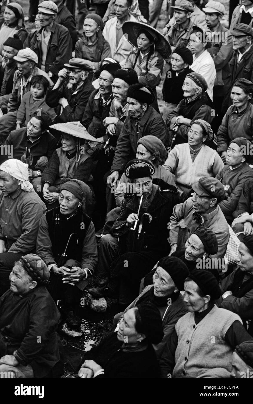 A CROWD of ethnic BAI PEOPLE watches a CHINESE OPERA PERFORMANCE in the farming town of DALI - YUNNAN, CHINA - Stock Image