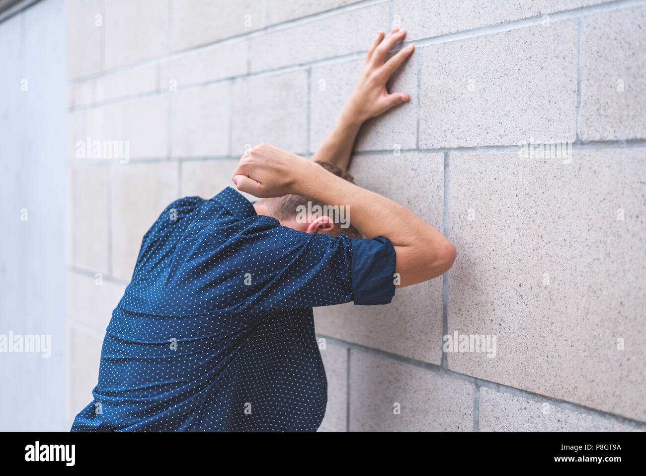 Teen punching brick wall in frustration. - Stock Image