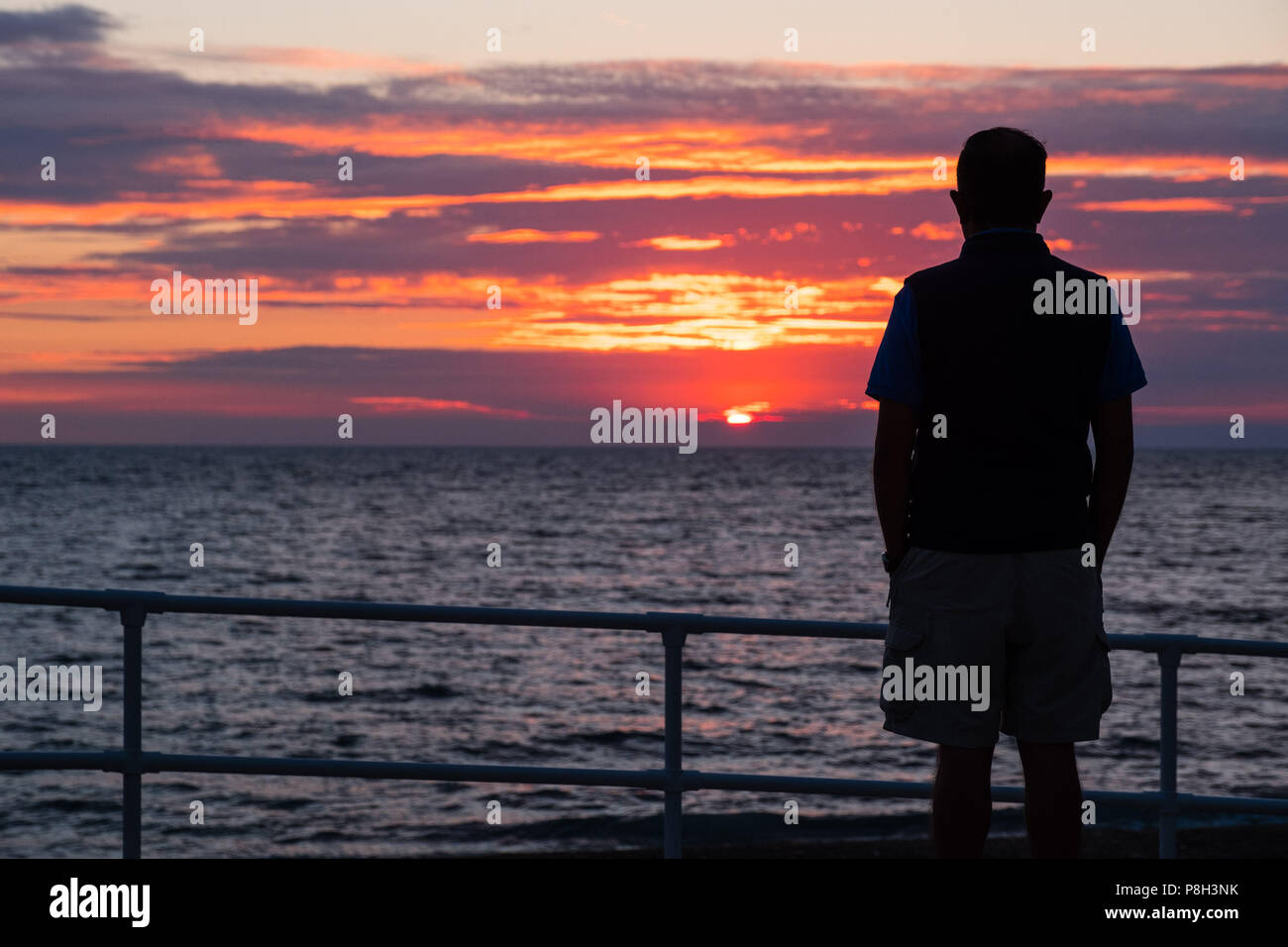 Aberystwyth Wales UK, 11 July 2018. UK Weather:  A man watches as the sun sets on yet another England football World Cup dream, with the team being beaten 2-1 by Croatia after extra time in the semi final. The years of hurt continue for a side who last won the tropy in 1966, and have not been further than the semi final since  then  photo © Keith Morris / Alamy Live News Stock Photo