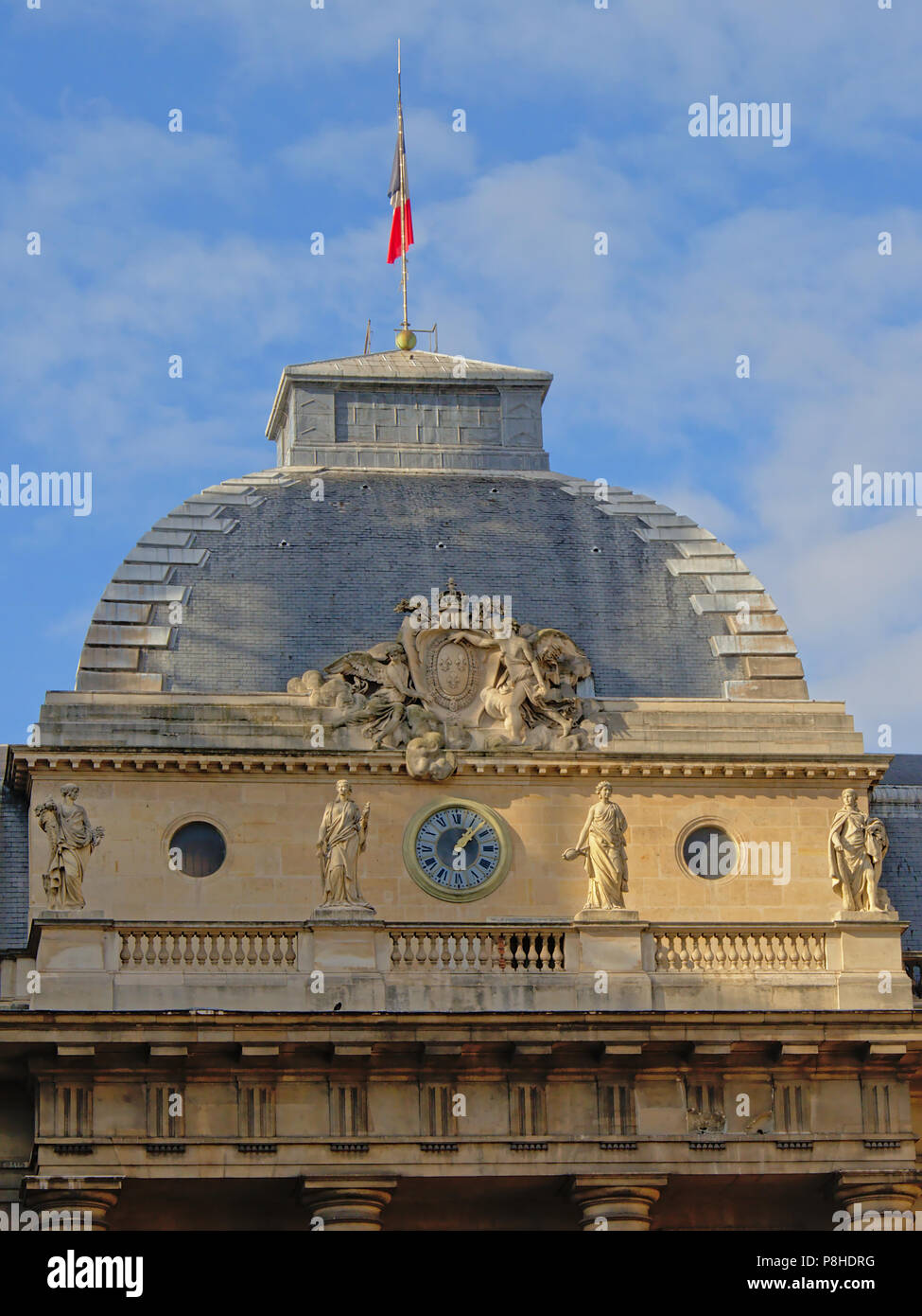 Detail of the Palace of Justice Paris, France: cupola with clock and stone sculptures - Stock Image