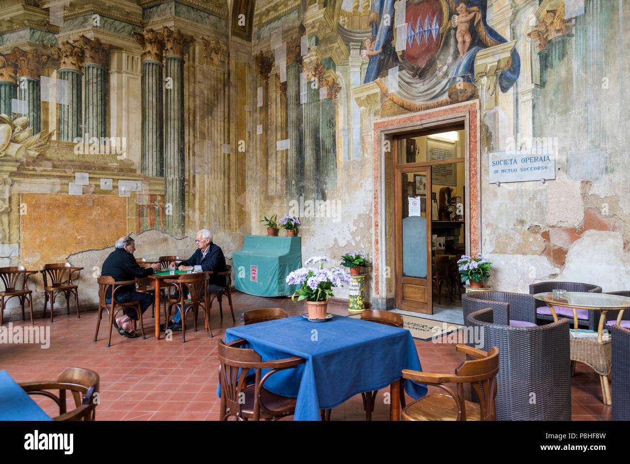 Sedile Dominova, a historic building with an open loggia with original frescos now serving as a working men's club, Two old men playing cards, Sorrent - Stock Image