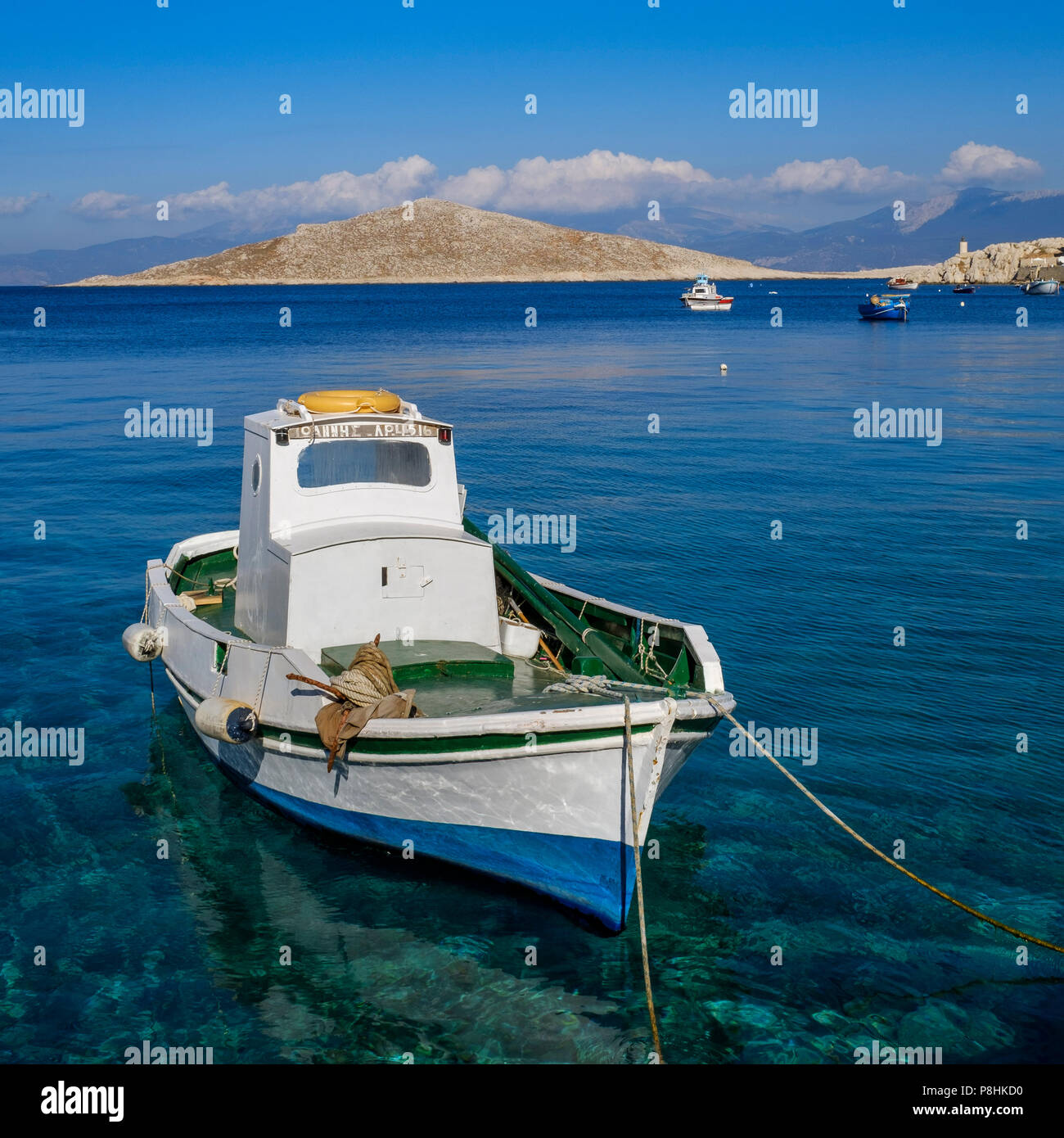 A small blue and white fishing boat in Halki harbor. - Stock Image