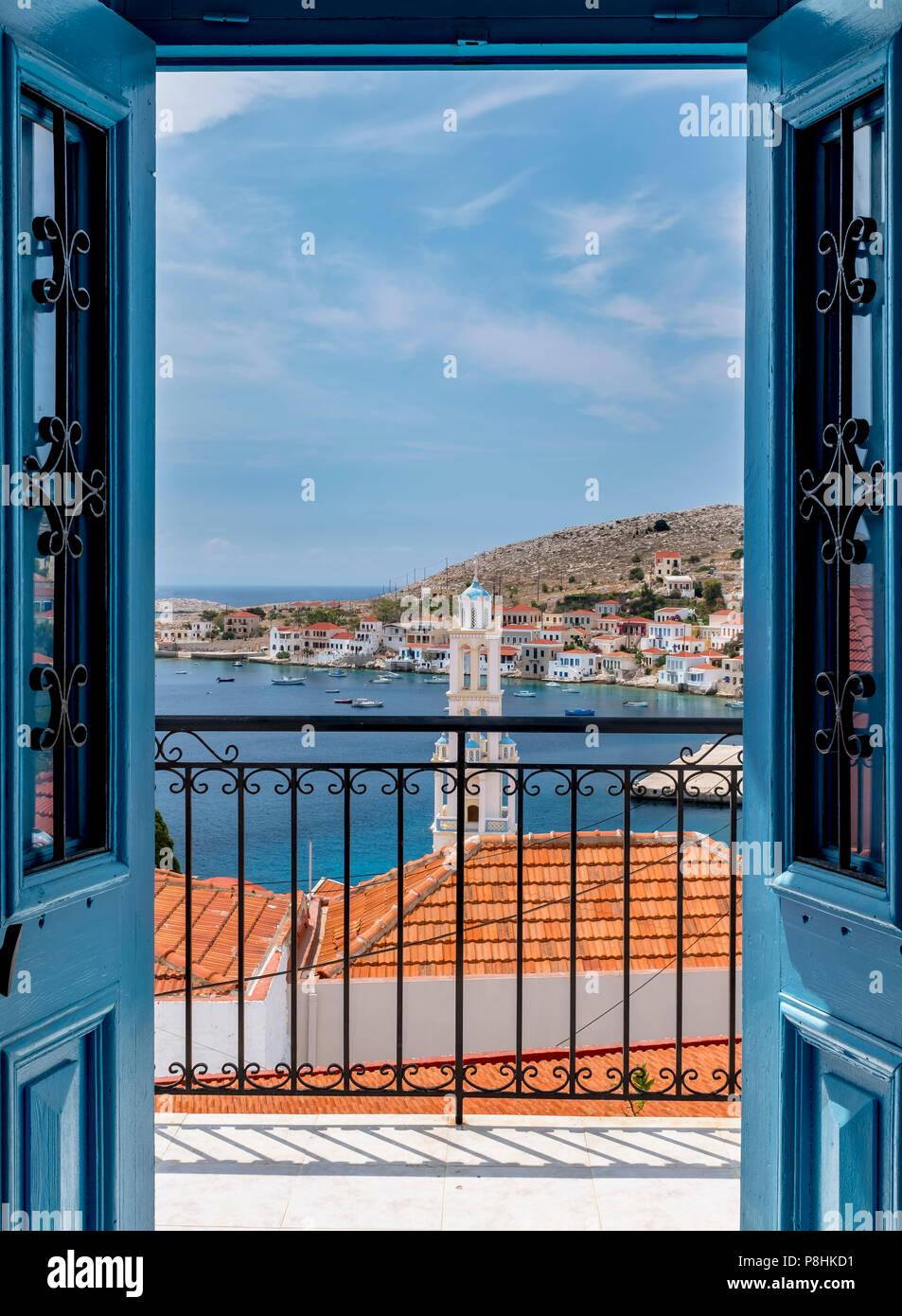 The best view of Halki harbor through a blue wooden door frame. - Stock Image