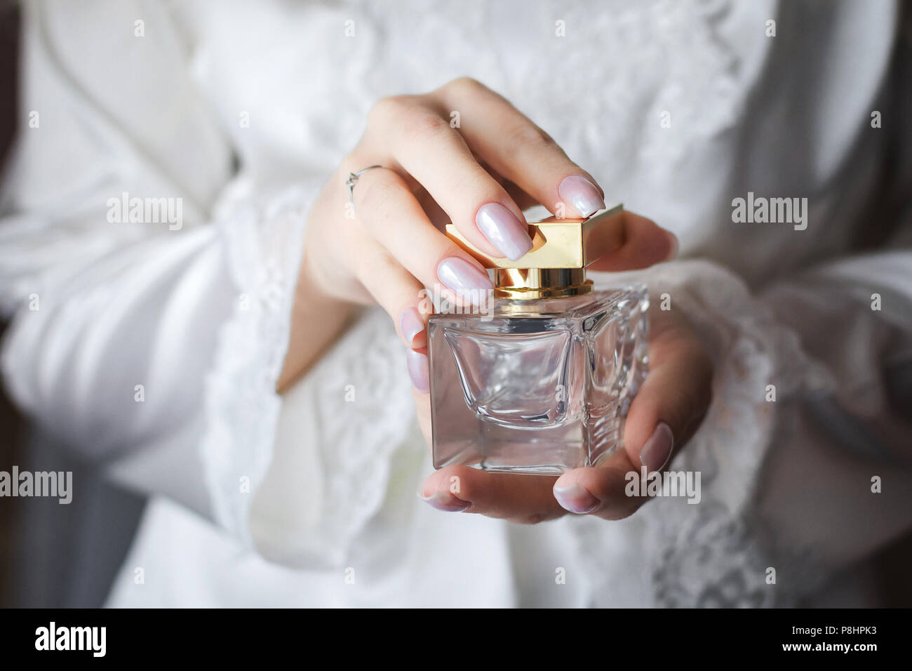 bride holding in hands a flacon of luxury perfume - Stock Image