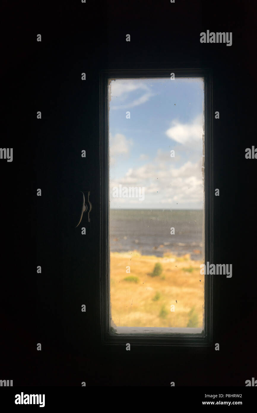 A glimpse of the Baltic Sea with sand dunes through a window on a lighthouse Stock Photo