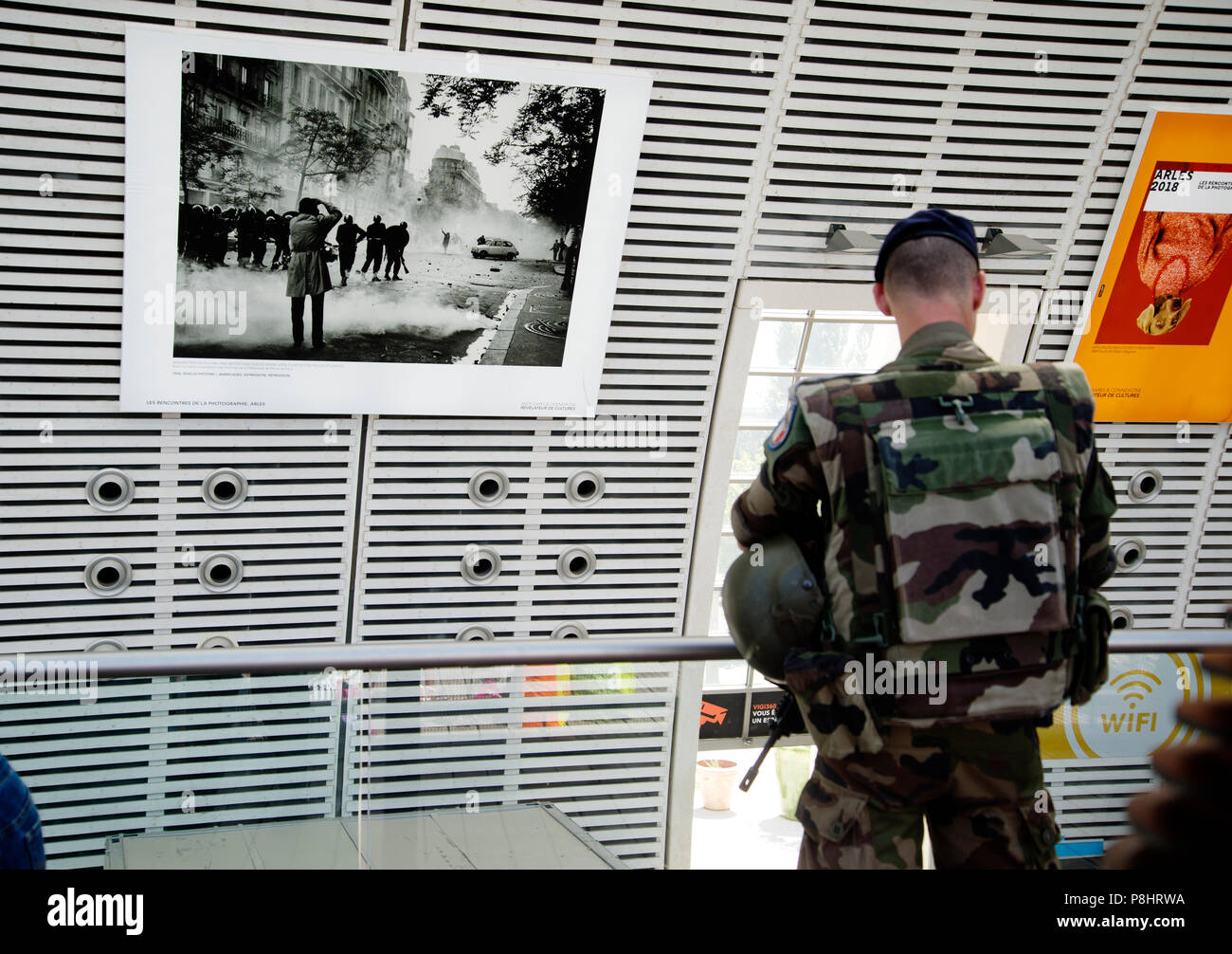 Avignon, France. TGV and Eurostar train station. An armed soldier on patrol inside the station which is decorated with photos from Arles photography f - Stock Image