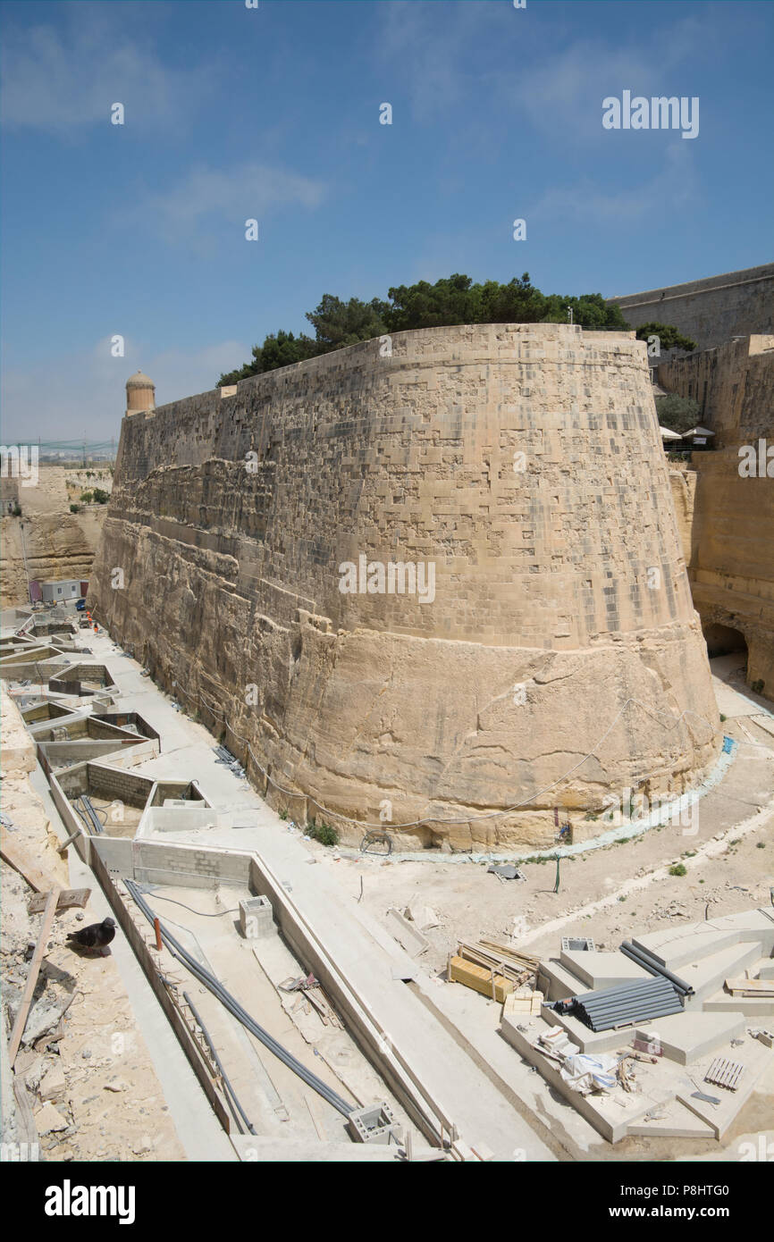 A pigeon surveys the development of the deep ditch in front of Valletta's cutain wall fortifications. - Stock Image