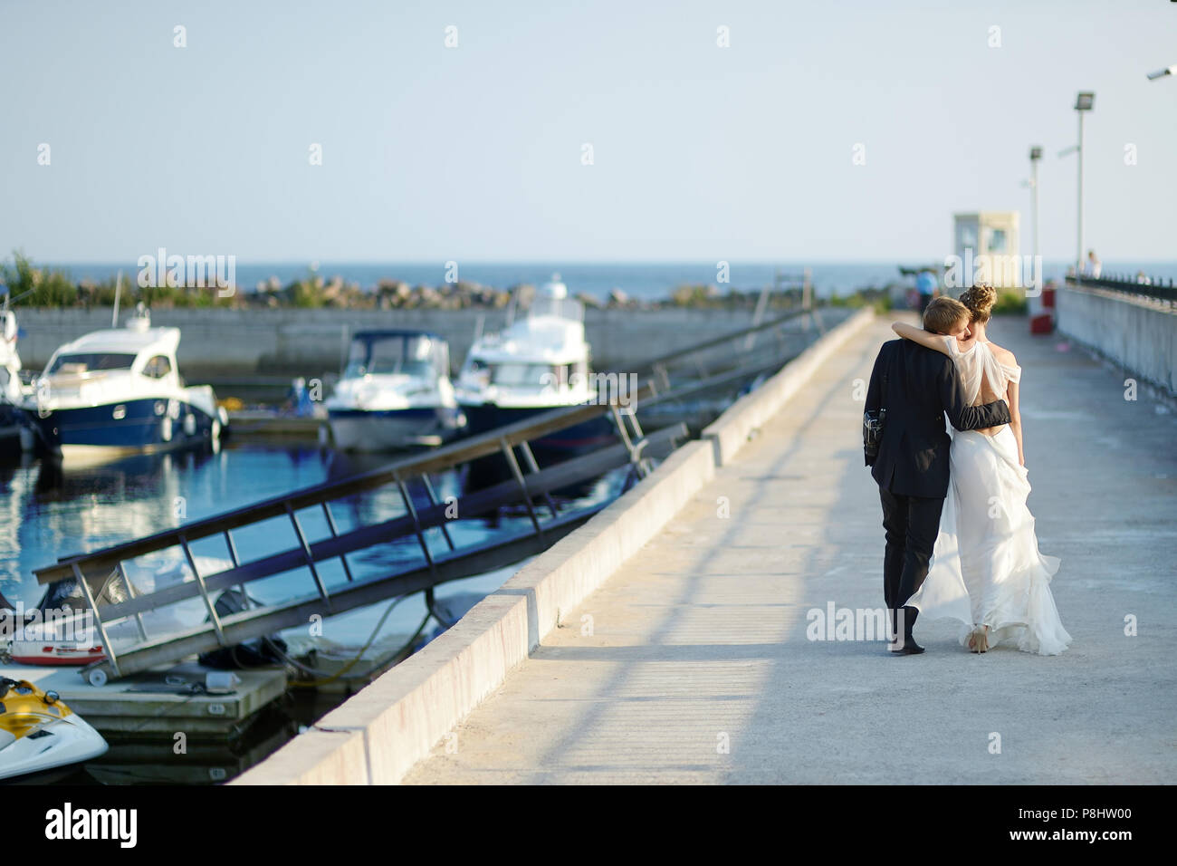 e2b19d1eac88d3 Happy bride and groom walking on pier in small harbor Stock Photo ...