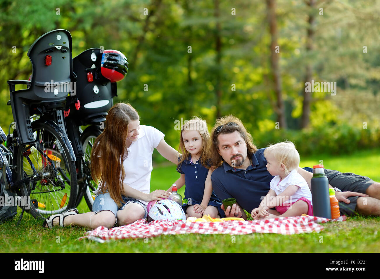 Happy family of four picnicking in the park - Stock Image