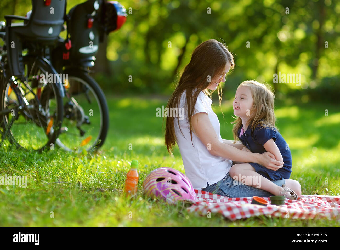 Young mother and her daughter picnicking in the park - Stock Image