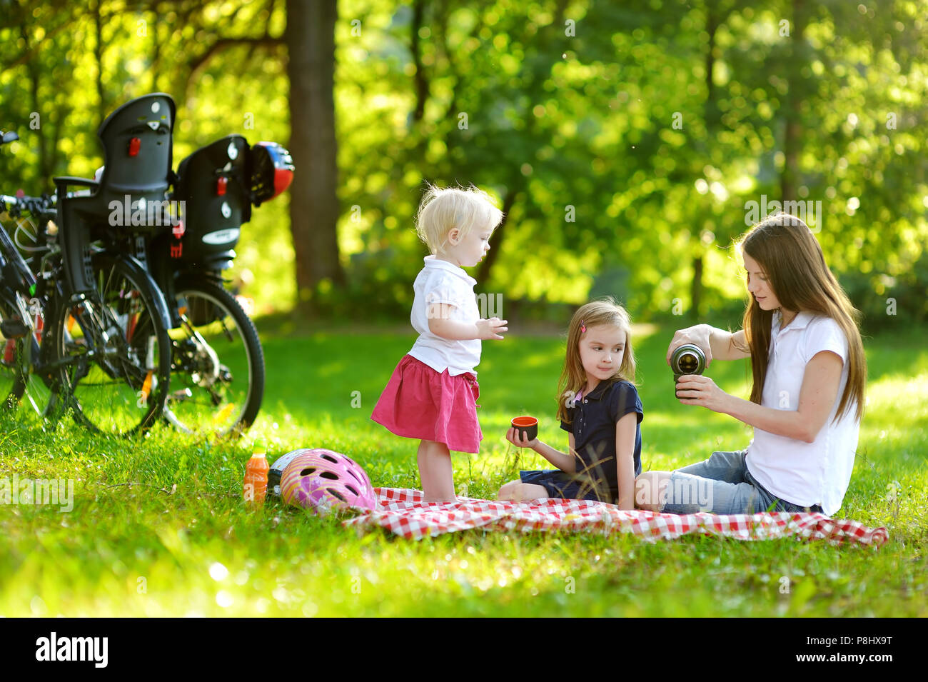 Young mother and her daughters picnicking in the park - Stock Image