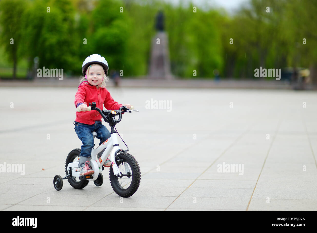 9866b58b2df Adorable toddler girl riding her first bike Stock Photo: 211837006 ...