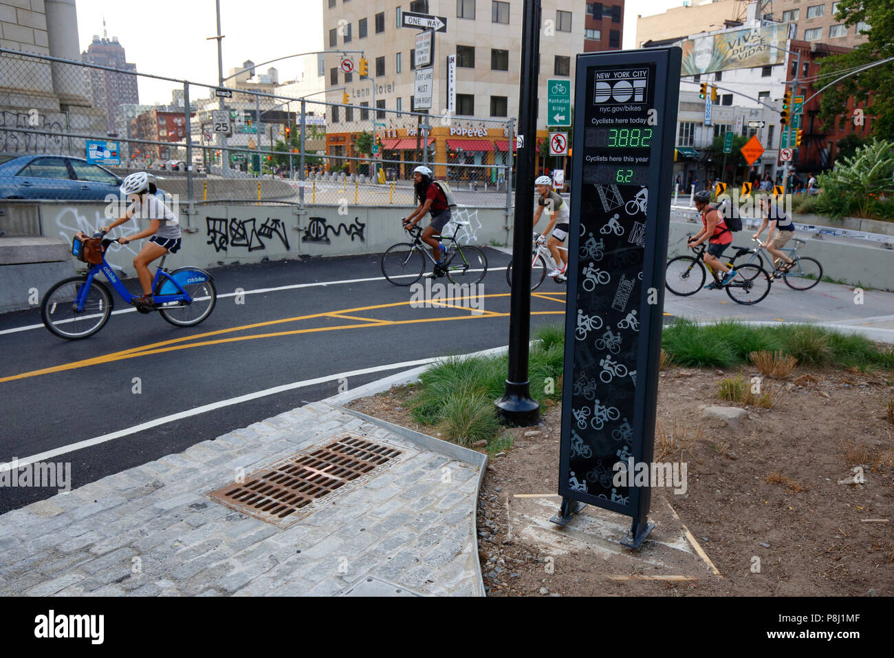 Bicyclists on the Manhattan Bridge cycle past NYC's first bicycle counter. - Stock Image