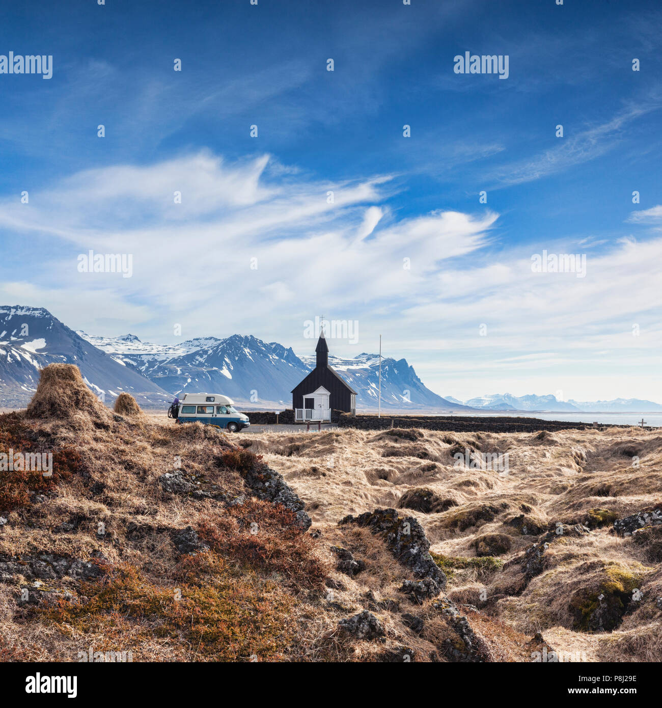 16 April 2018: Budir, Snaefellsnes Peninsula, West Iceland - The Black Church and a Volkswagen campervan with bikes on the back, with moss covered... - Stock Image