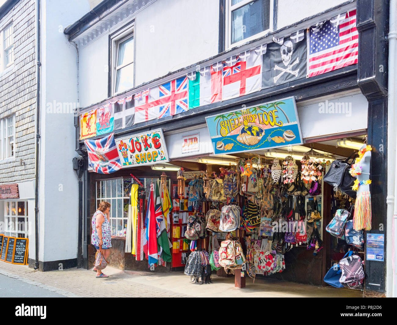 6 June 2018: Looe, Cornwall, UK - Shops in Buller Street, with a Joke Shop and a Shell Shop. Woman looking in window. - Stock Image