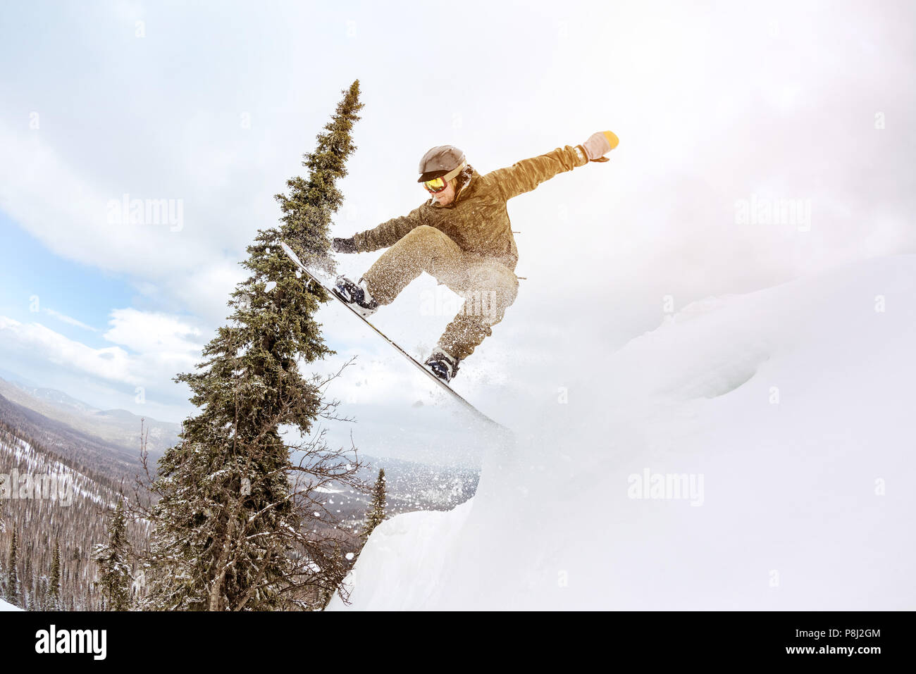 Snowboarder jumps from big snowdrift at offpiste forest slope. Freeride concept - Stock Image