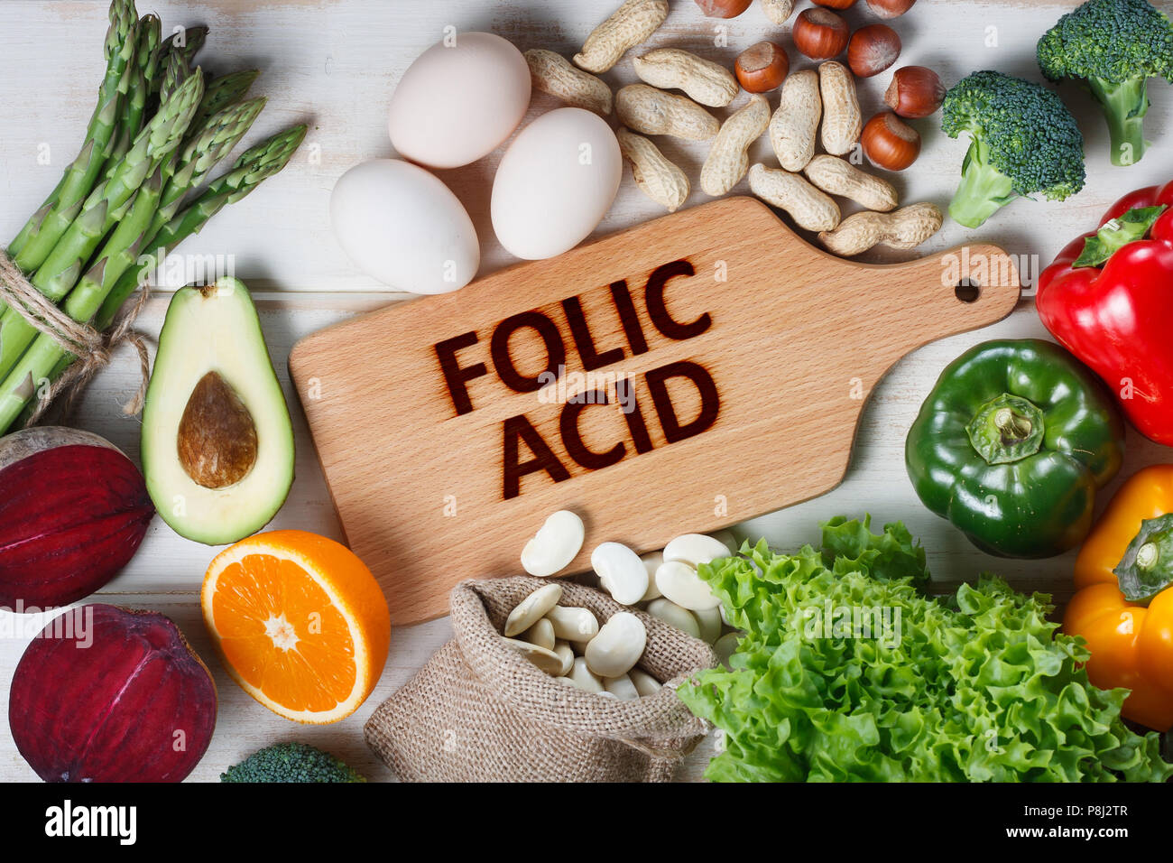 Natural sources of folic acid as asparagus, broccoli, eggs, salad, avocado, paprika, nuts, orange, beetroots and beans - Stock Image