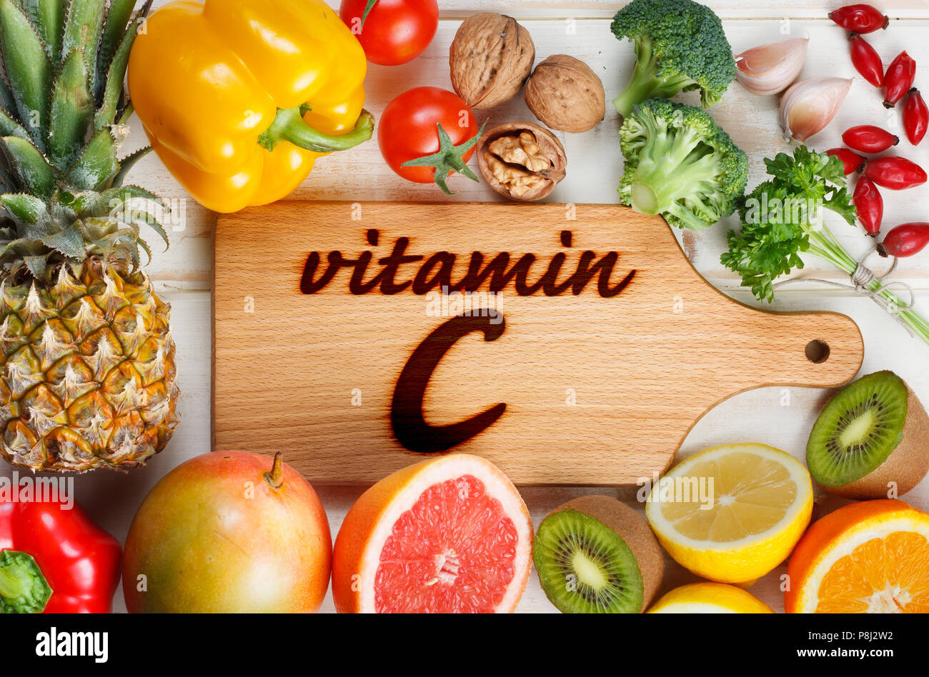 Vitamin C in fruits and vegetables. Natural products rich in vitamin C as oranges, lemons, dried fruits rose, red pepper, kiwi, parsley leaves, garlic - Stock Image